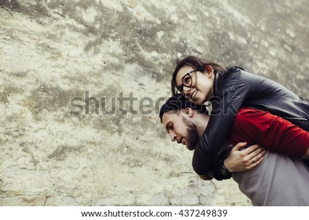 man carries his girlfriend on his back - stock photo