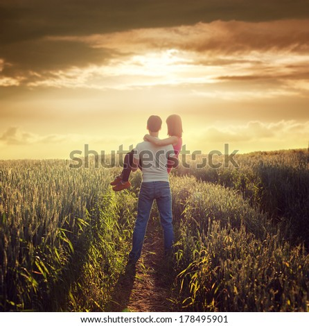 Man Carries Woman at Summer Field in Sunset. Romantic Love and Care Concept. Copy Space. Toned Photo. - stock photo