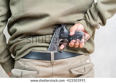 man carry hidden gun - stock photo