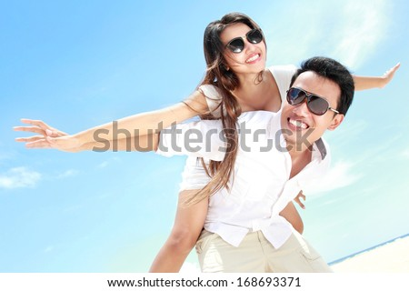 Man carry the girl on his back having fun together on the beach - stock photo
