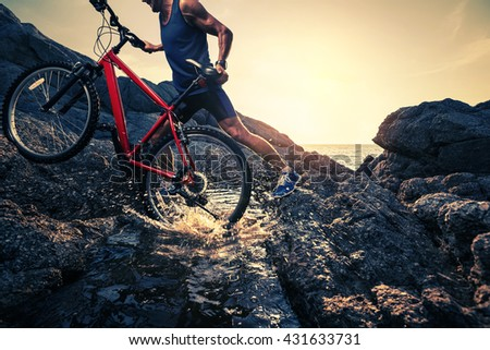 Man carrying a bike on the rock through water during sunset
