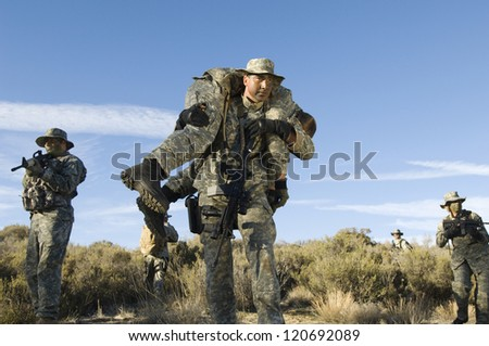 Man carrying a injured female solider on shoulder - stock photo