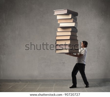 Man carrying a stack of books - stock photo