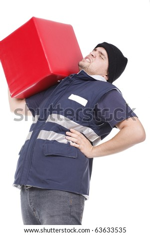 man carrying an heavy and red cube with pain on his back - stock photo