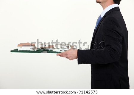 Man carrying architect model - stock photo