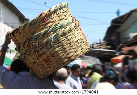 man carrying baskets at the market - stock photo