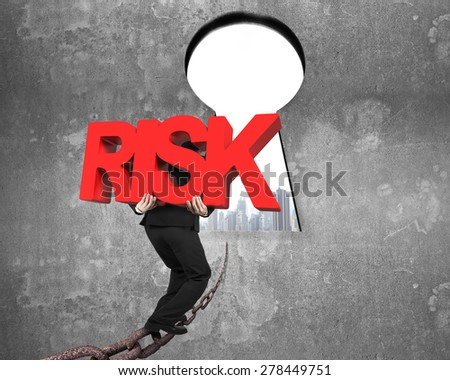 Man carrying big red RISK 3D word walking on old iron chain toward keyhole door, with urban scene view and gray concrete wall background - stock photo