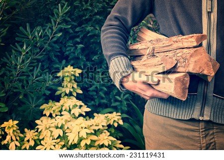 Man carrying firewood logs, vintage process - stock photo