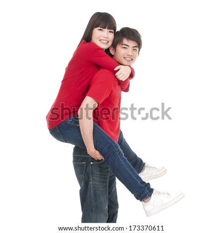 man carrying girlfriend on his back - stock photo