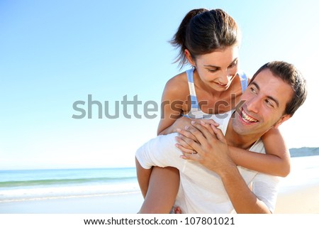 Man carrying girlfriend on his back at the beach - stock photo