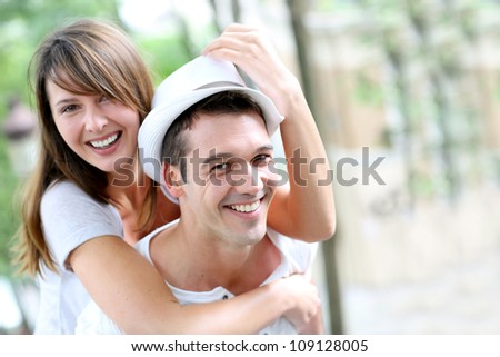 Man carrying girlfriend on his back in public park - stock photo