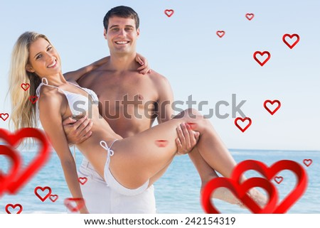 Man carrying his pretty girlfriend smiling at camera against hearts - stock photo