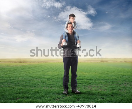 Man carrying his son on his shoulders on a green meadow - stock photo