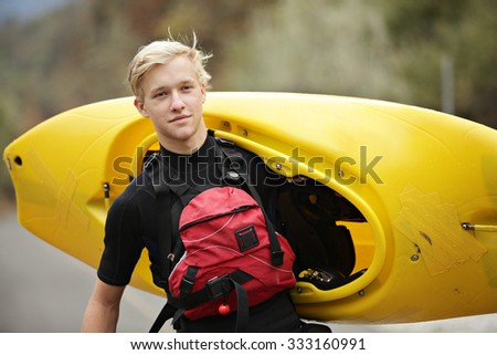 Man carrying his whitewater play boating kayak - stock photo