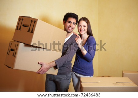 Man carrying moving boxes and woman leaning onto him - stock photo