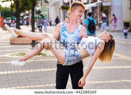 Man carrying on his lap his pretty girlfriend on the walking street - stock photo
