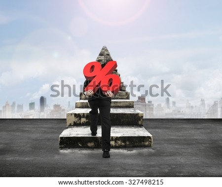 Man carrying percentage sign climbing old concrete stairs, with sunny sky background. - stock photo