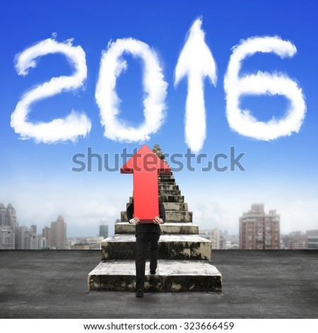Man carrying red arrow up sign climbing old concrete stairs toward white 2016 shape clouds in sky. - stock photo