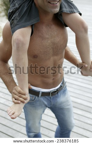 Man Carrying Son on His Shoulders - stock photo