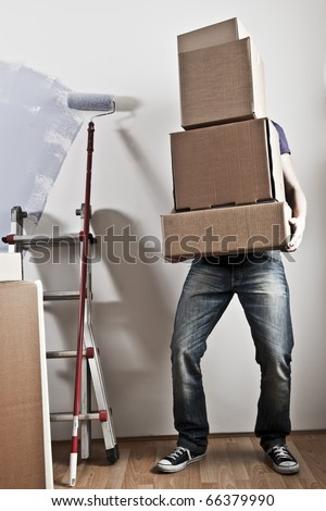 Man Carrying Stacked Boxes on moving day, desaturated image - stock photo