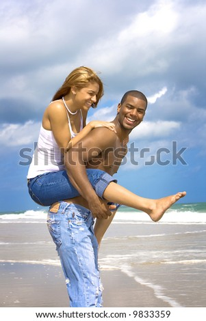 Man carrying woman on his back on a beach. - stock photo