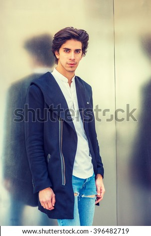 Man Casual Fashion. Portrait of American college student in New York. A handsome guy wearing fashionable long coat, jeans, standing against metal wall, looking at you. Instagram filtered effect.  - stock photo
