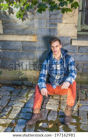 Man Casual Fashion. Wearing a blue and white pattern shirt,  a blue hood vest,  red jeans, brown leather boot shoes, a young guy is sitting on the ground against the wall, relaxing.