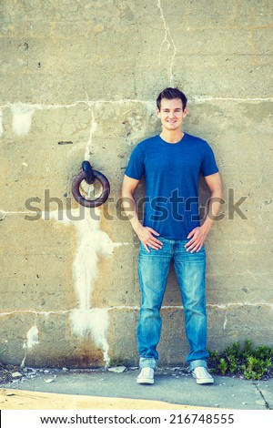 Man Casual Fashion. Wearing a blue T shirt, jeans, white sneakers, a young handsome guy is standing against an old concrete wall with a rusty metal ring, charmingly looking at you. - stock photo