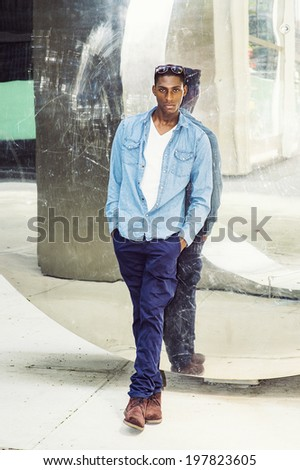 Man Casual Fashion. Wearing a white under wear, long sleeve shirt, blue pants, brown boot shoes, glasses on head, a young black guy is standing back against a mirror wall, casually looking at you.  - stock photo