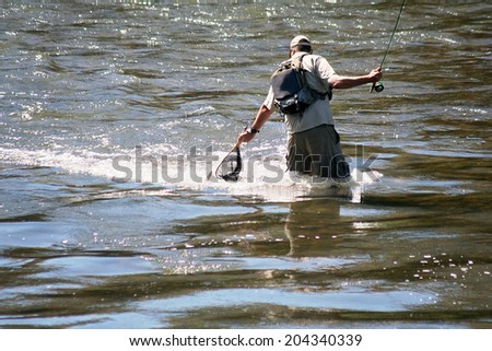 man catching trout in a river - stock photo