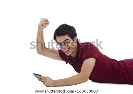 Man celebrating his success while playing game on a mobile phone - stock photo