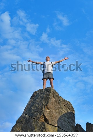 Man celebrating reaching the top of a mountain standing on top of a high rock pinnacle with his arms outstretched rejoicing - stock photo