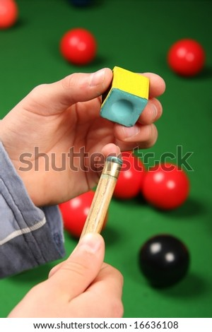 Man chalking the end his snooker cue with table and balls in background - stock photo