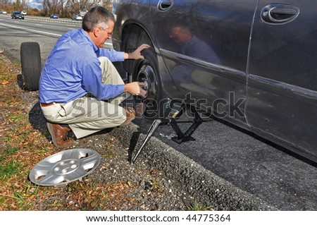 Man changing flat tire along a busy highway - stock photo
