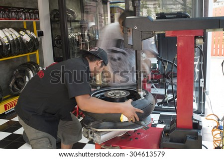 Man changing tire from their small business, Mahasarakham,Thailand ,4th August 2015 - stock photo