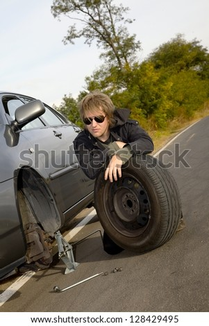 Man changing tires on car - stock photo