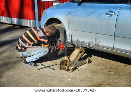 Man changing tires on the car at the service station - stock photo