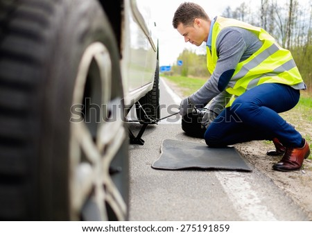 Man changing wheel on a roadside  - stock photo