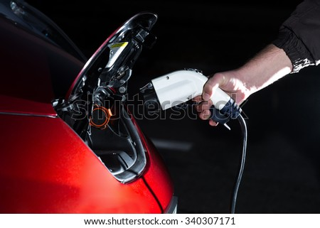 Man charged electric car in the evening - stock photo
