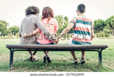 man cheating on her girlfriend at the park. he gives the hand to the man sitting next to his girlfriend. conceptual image - stock photo