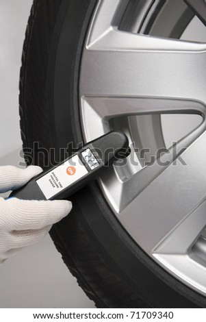 Man check the pressure in a car tire with digital meter - stock photo