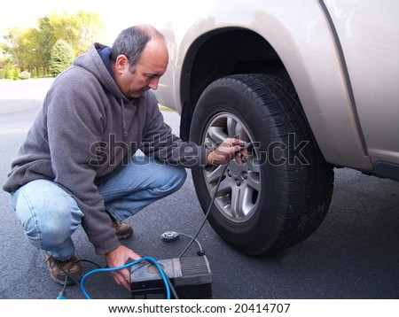 man checking air pressure in truck tire