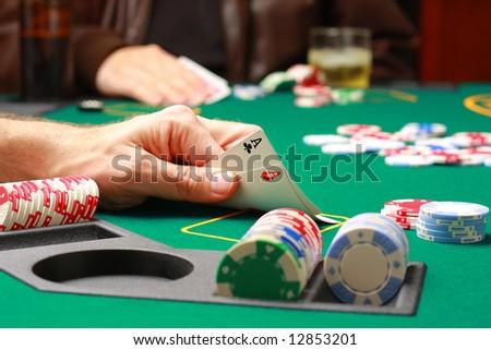 Man checking cards during poker game - stock photo