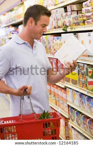 Man checking food labelling on supermarket products