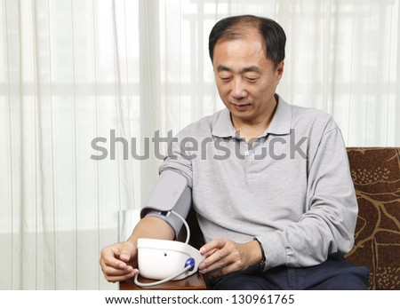 Man checking his blood pressure at home - stock photo