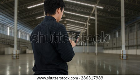 Man checking in empty warehouse using tablet.