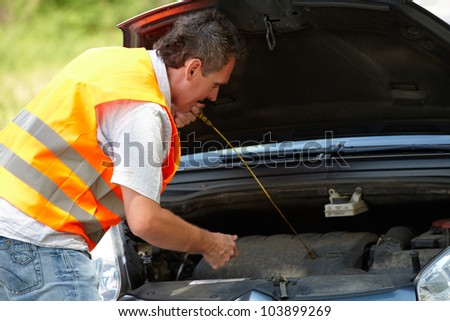 Man checking level of oil on a car engine dipstick - stock photo