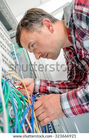 Man checking server wiring - stock photo