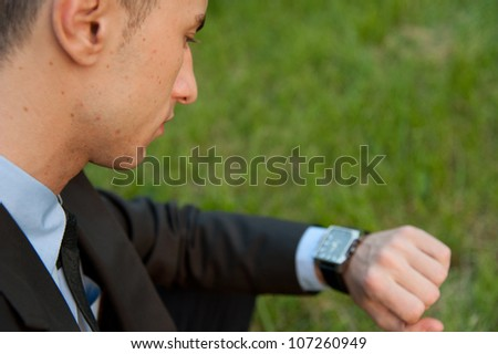 Man checking the time on the background of park - stock photo