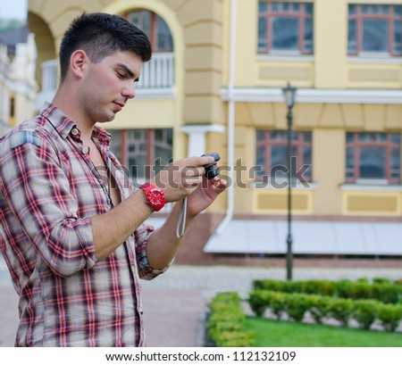 Man checking the viewfinder at the back of a camera to check the photograph that he has just taken - stock photo